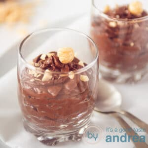 Two glasses with chocolate mousse topped with hazelnuts, square