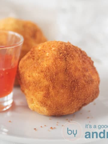 a square photo with papas rellenas and a glass filled with chili sauce