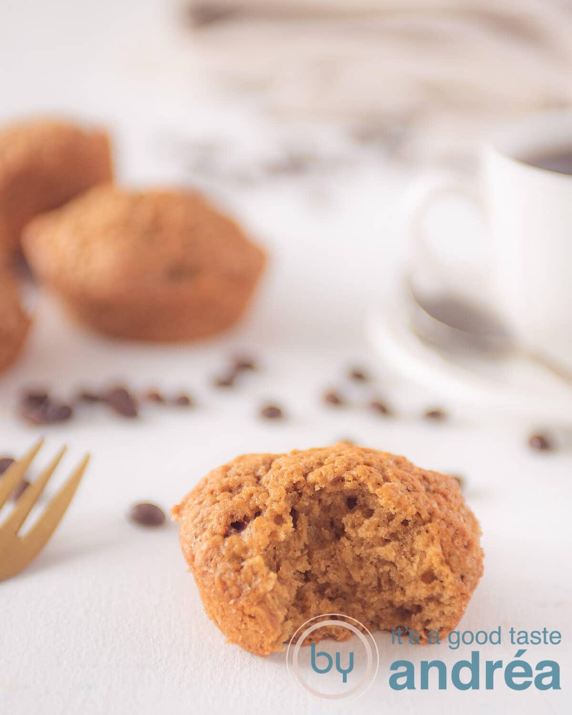 Een koffie muffin met een hap eruit. Wat muffins op de achtergrond