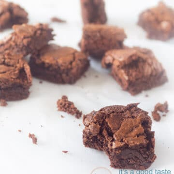 Homemade chocolate brownies on a white suface. The front one has taken a bite out.