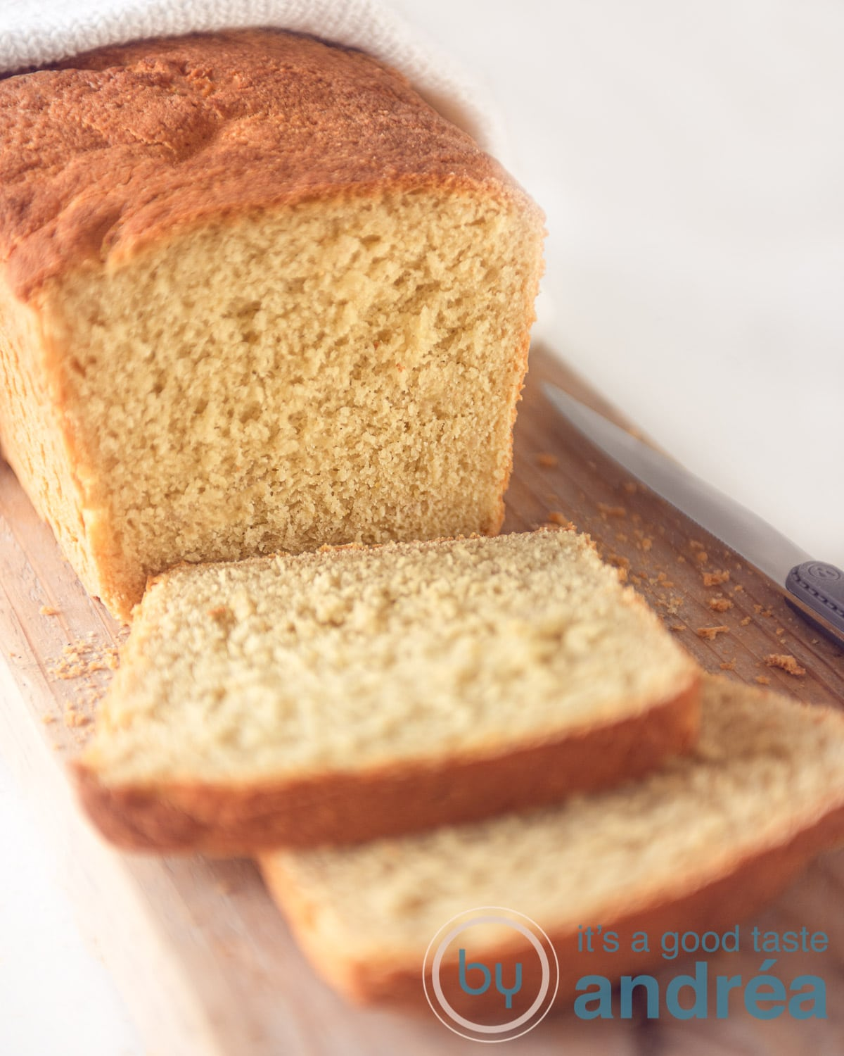 A loaf cornbread on a wooden bord. Two slices cut off.