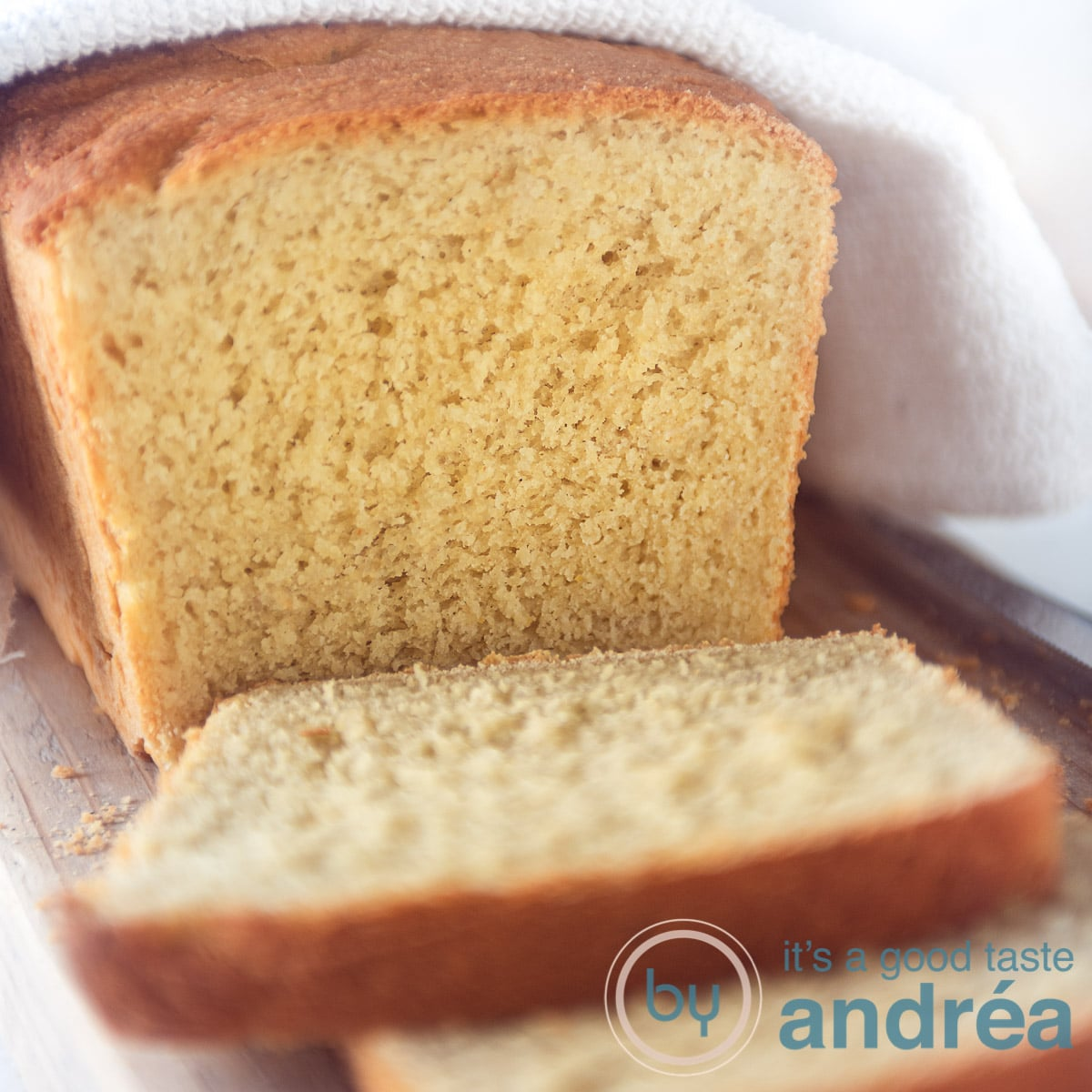 a square photo with cornbread. A white towel on top. Some slices cut off
