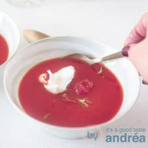Vierkante uitsnede van een kom soep met Italiaanse tomatensoep met mascarpone. Een hand neemt een hap