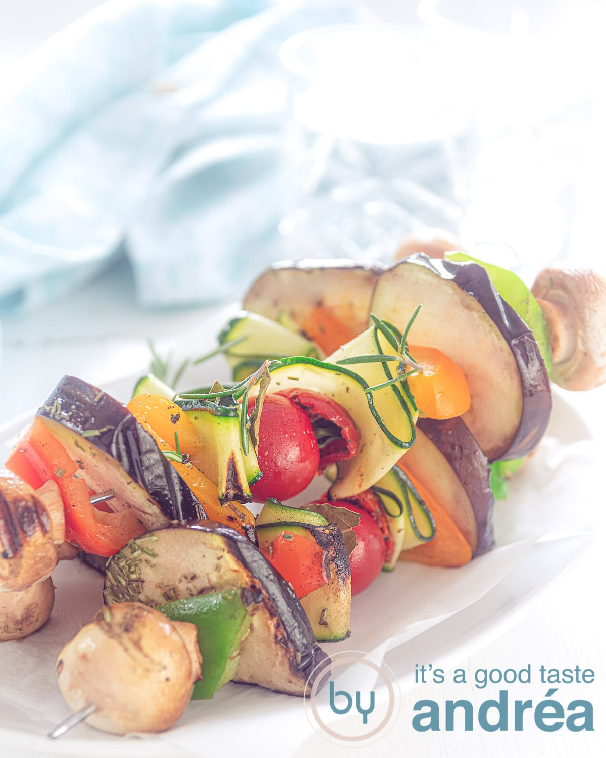 three vegan vegetable kebabs grilled, on a white plate. A Blue towel in the back