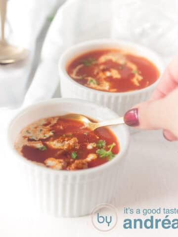 Two white bowls filled with tomato soup with meatballs and a dollop of cream. A hand with a spoon taking a bite.
