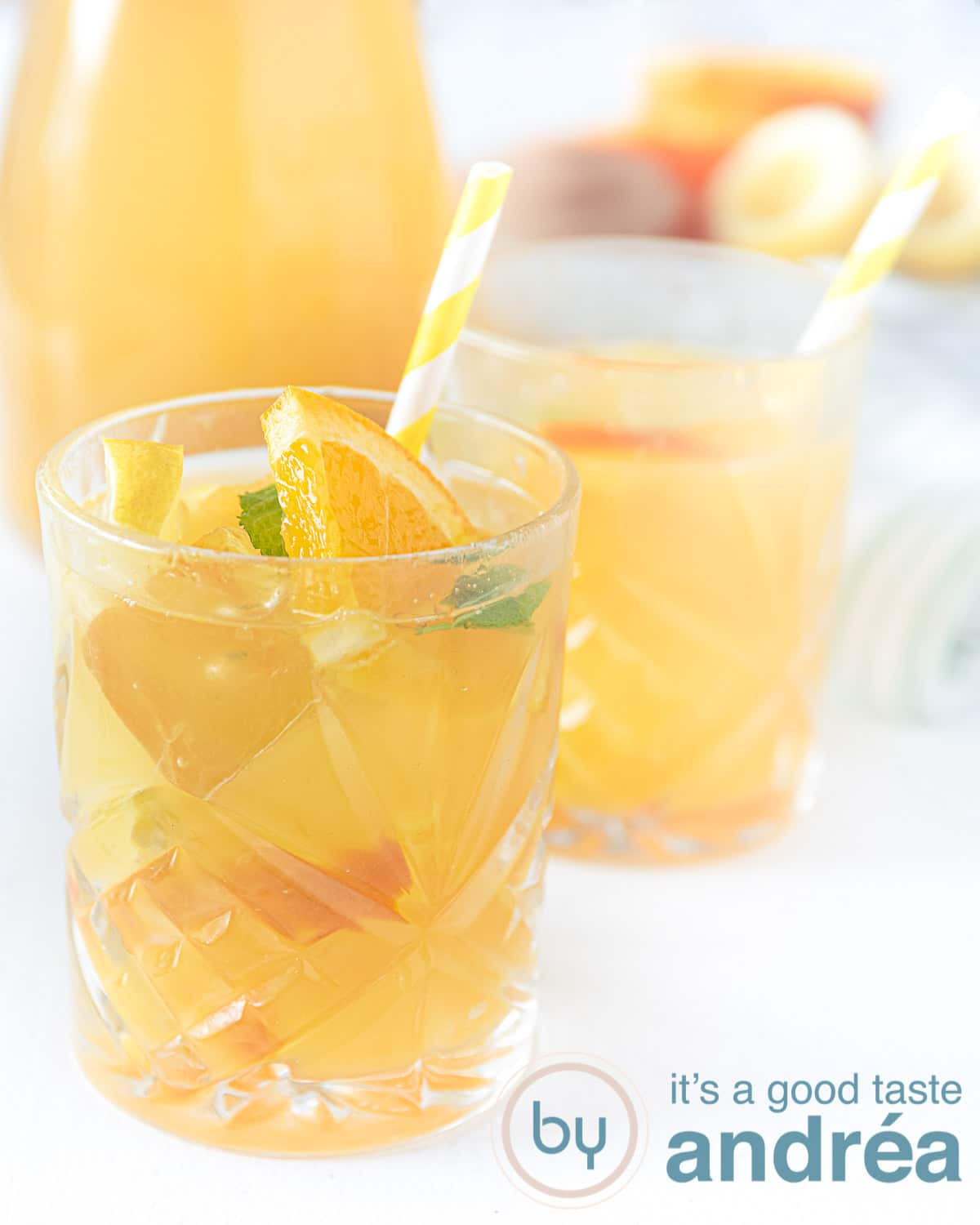 Two glasses filled with orange iced tea. A jar in the background and some oranges.