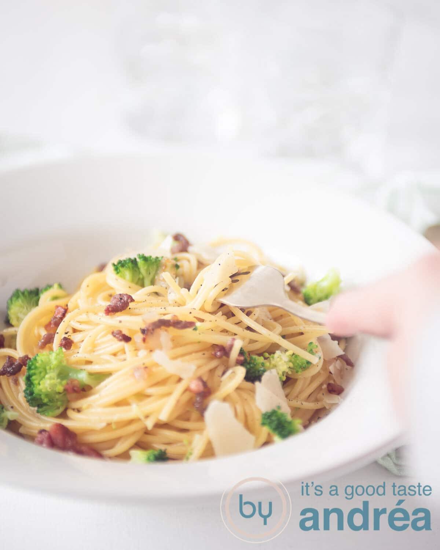 Een wit diep bord met pasta met broccoli, spekjes en gehakt