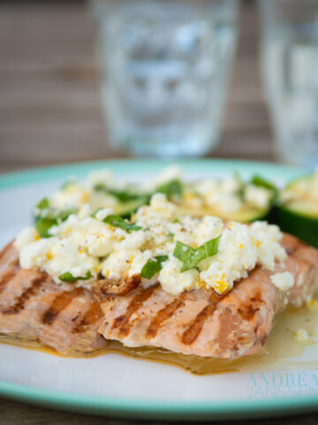 A grey plate with salmon and courgette with a feta dressing