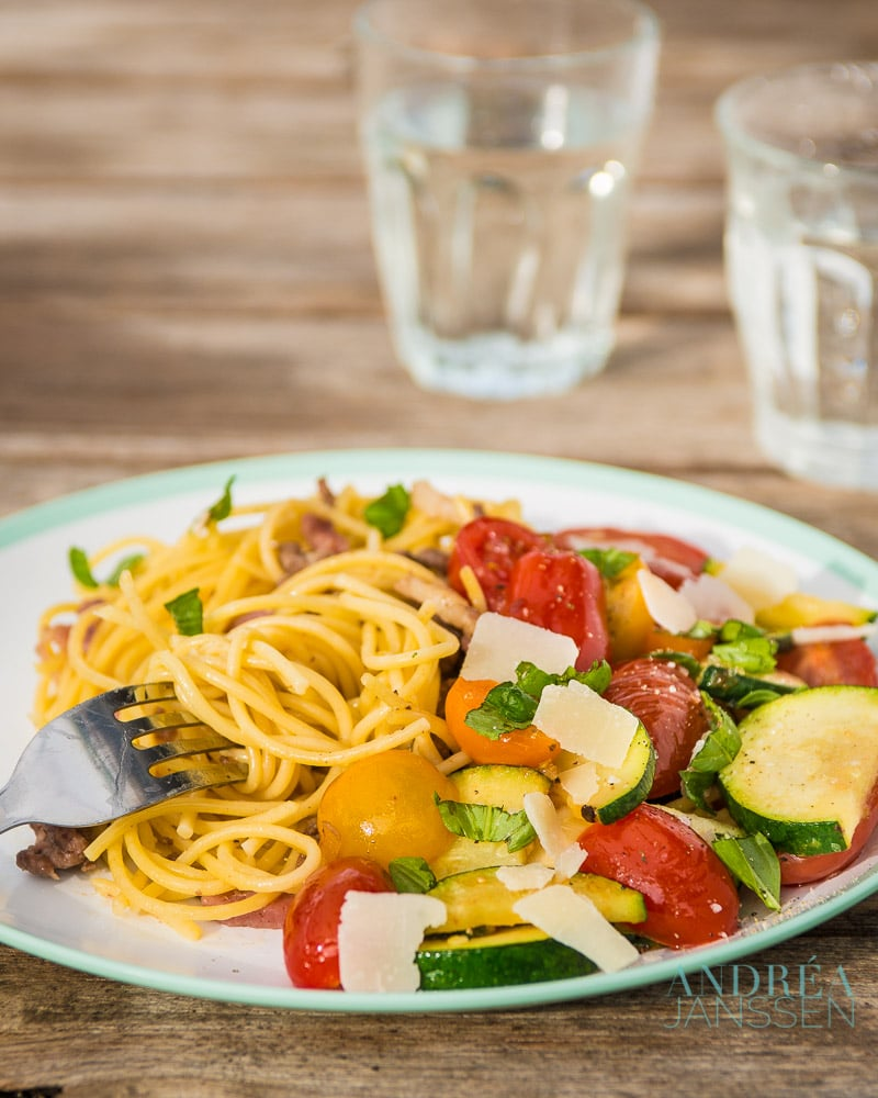 Spaghetti with stir-fried zucchini on a plate and two glasses of water
