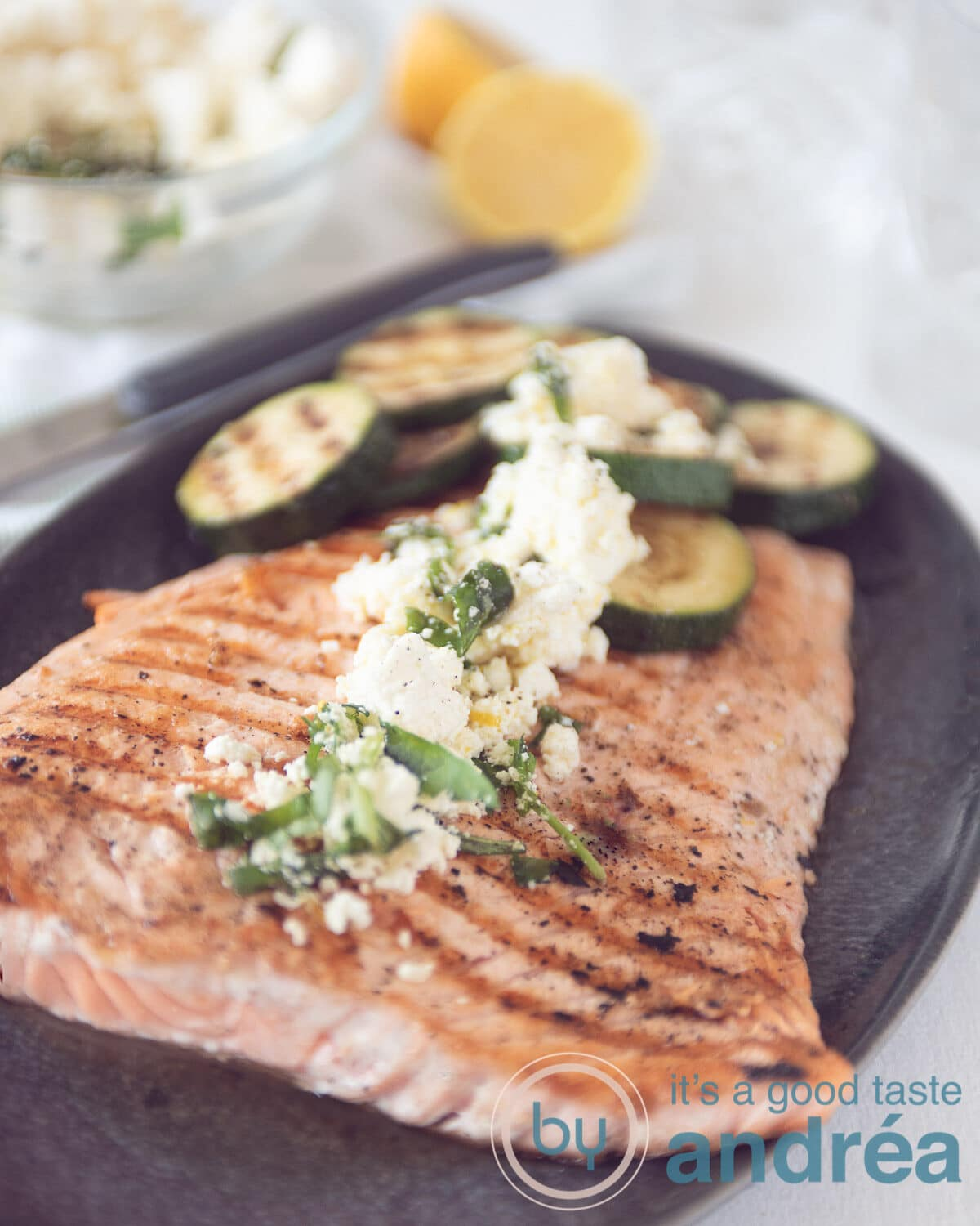 a large salmon, grilled and zucchini with a feta dressing on top