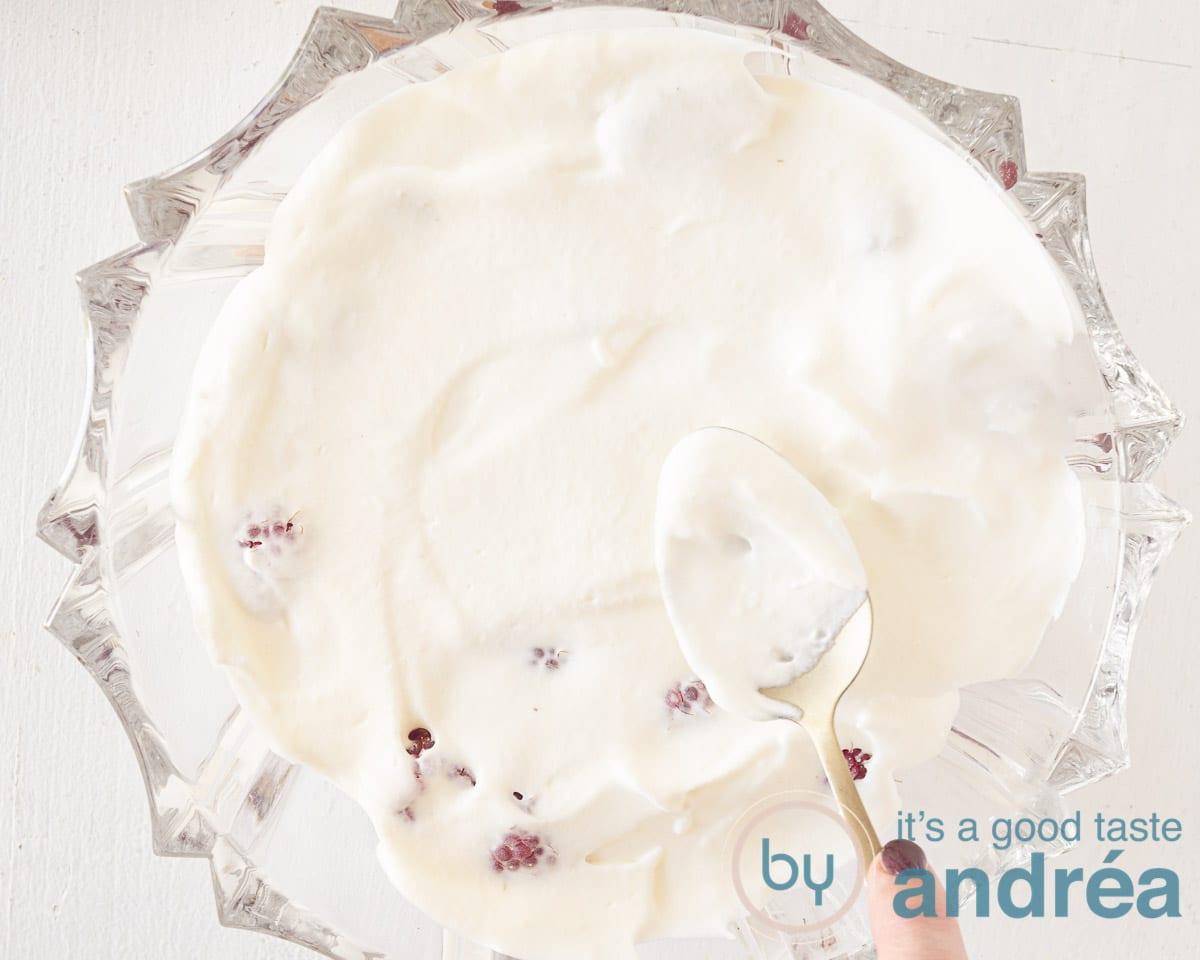 Bedek de frambozen met een laag vanille slagroom.