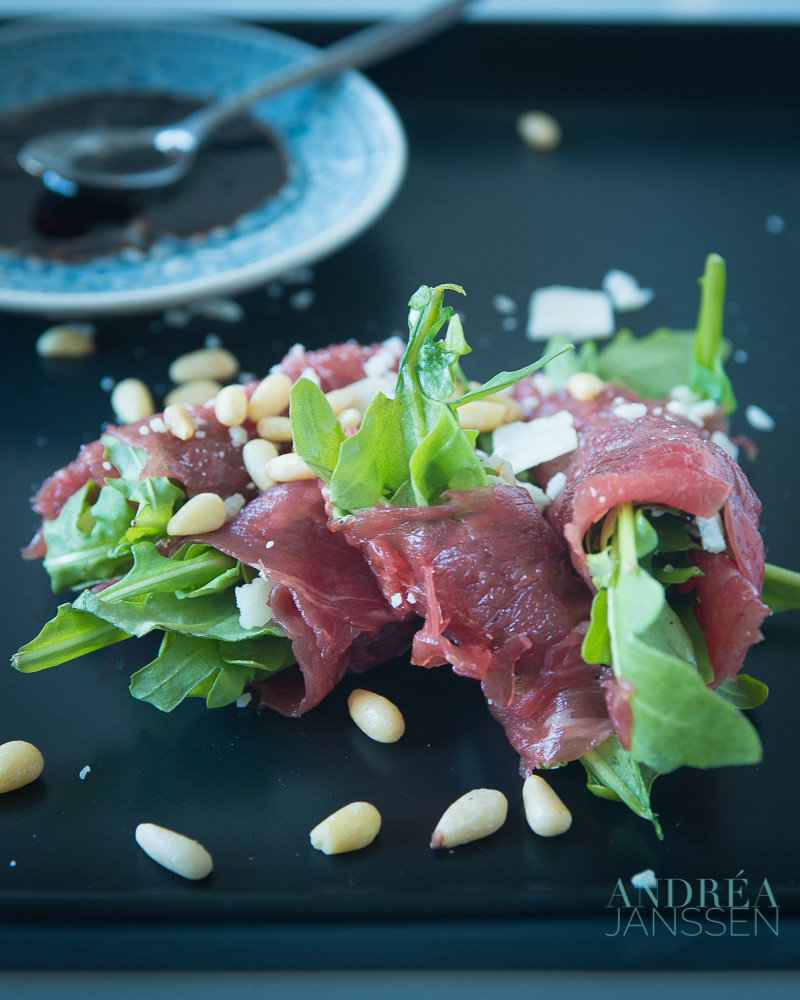 Beef carpaccio roll on a black plate