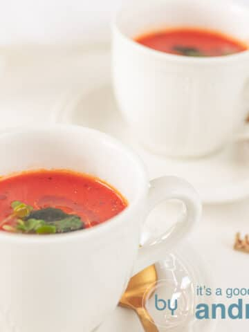 a square picture with two cups of homemade tomato soup