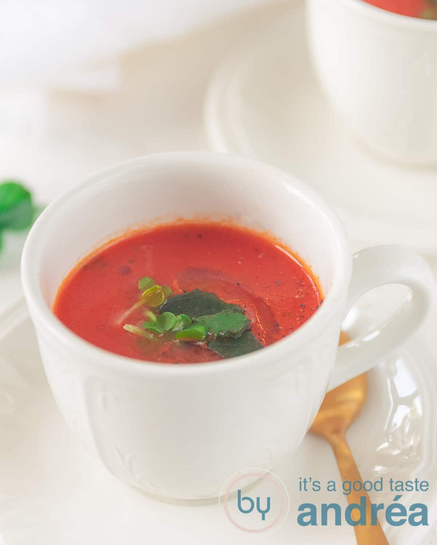Een kopje met tomatensoep met olijfolie en verse kruiden
