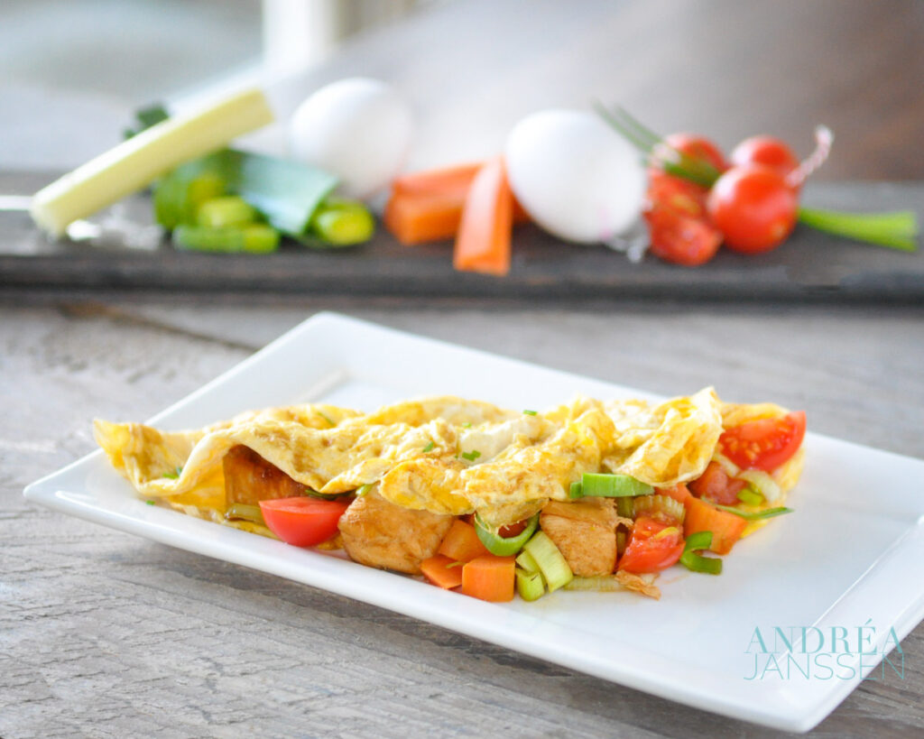 Filled omelet with chicken and vegetables on a plate