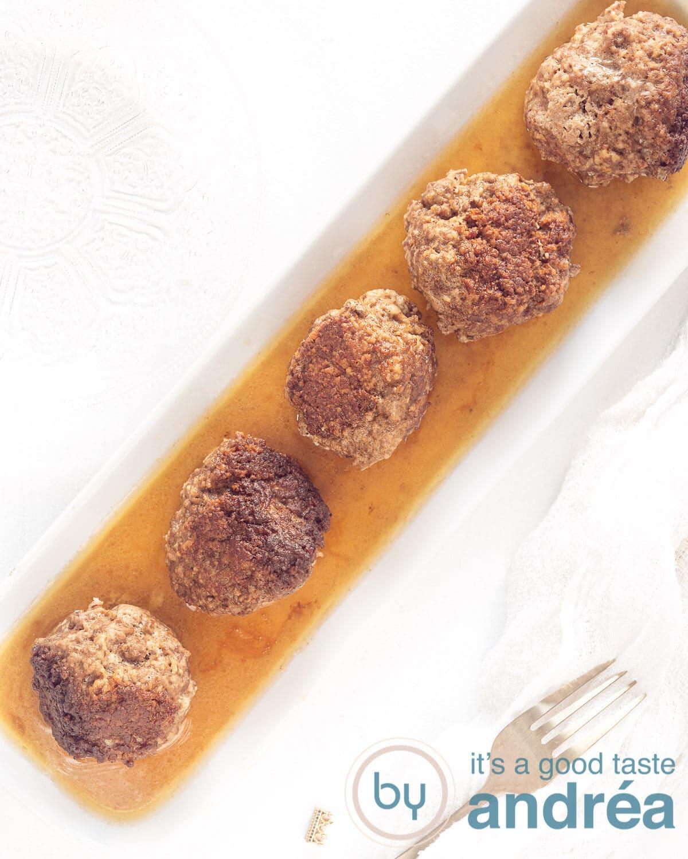A white platter full of meatballs lying in the gravy.