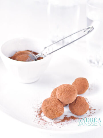 Orange chocolate truffles on a white plate with cocoa