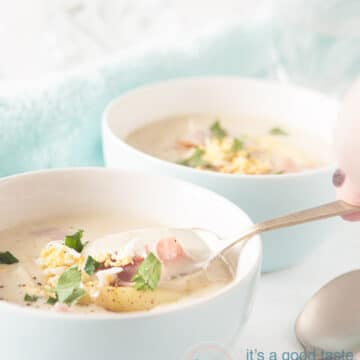 a white bowl with Asparagus soup with ham and grated egg and a spoon taking a bite