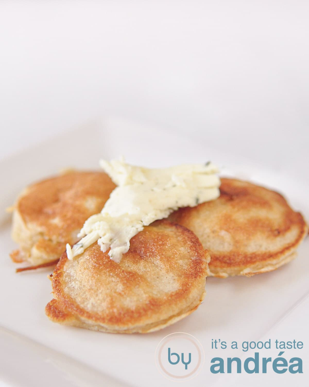 Fritters with garlic butter on a white plate