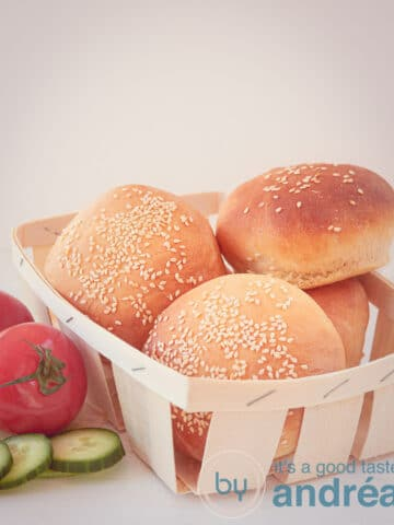 Hamburger buns in a wooden box, with tomatoes and cucumber