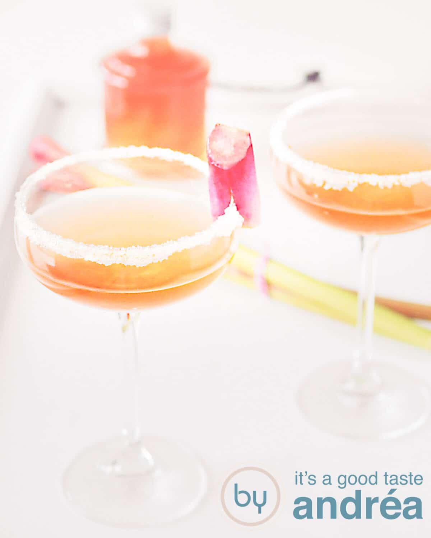 twee glazen champagne rabarber cocktail (en rabarber siroop op de achtergrond)