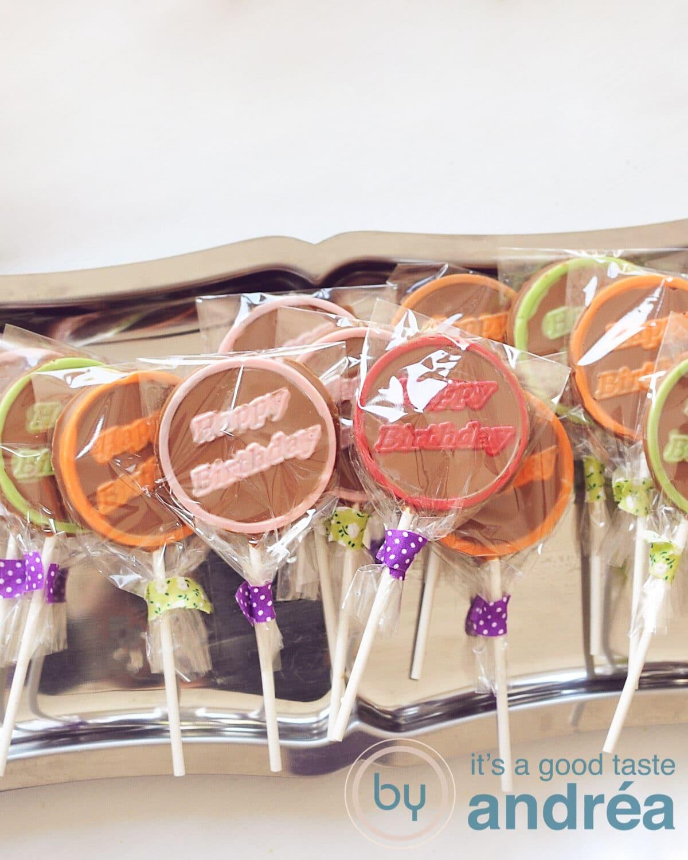 een schaal vol met chocolade lollies met happy birthday erop