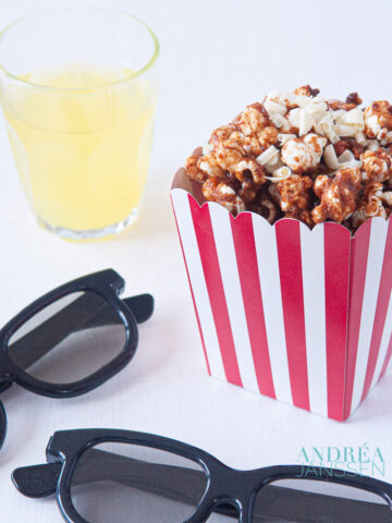 a jar with popcorn, a drink and two movie 3d glasses