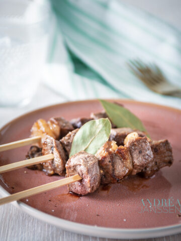 three Portuguese entrecote skewers on a pink plate with bay leaves