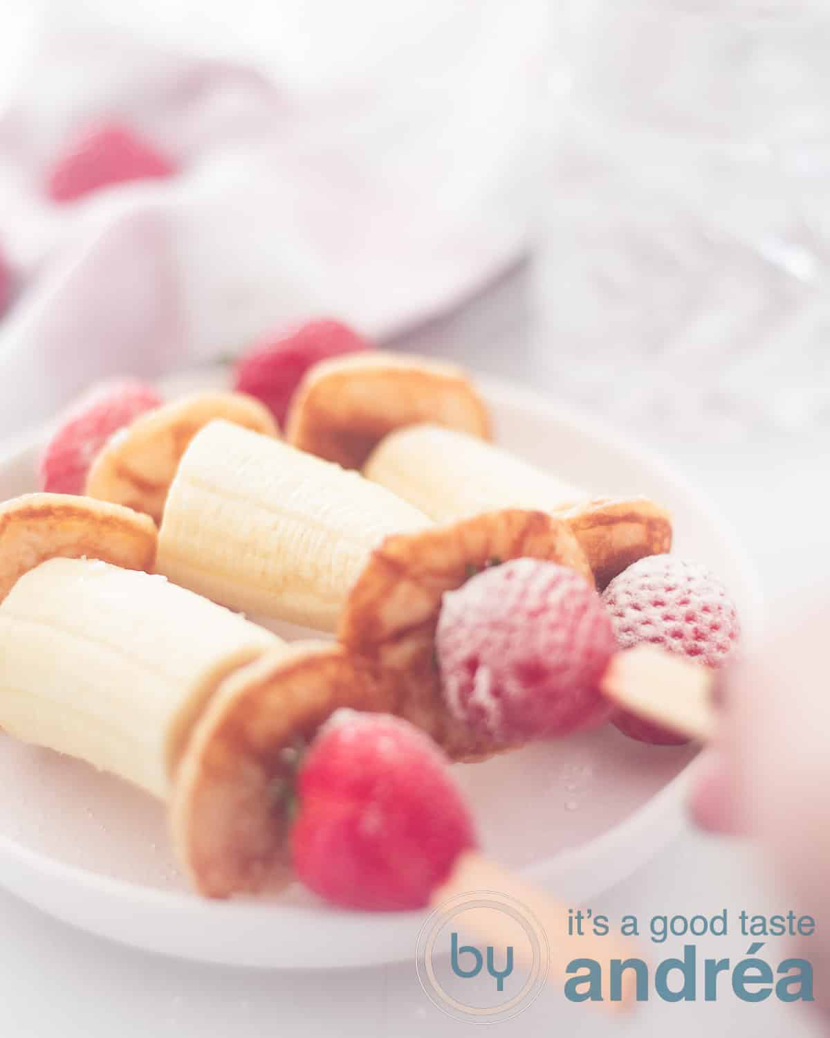 3 healthy treats with banana strawberries and pancakes on a stick on a plate