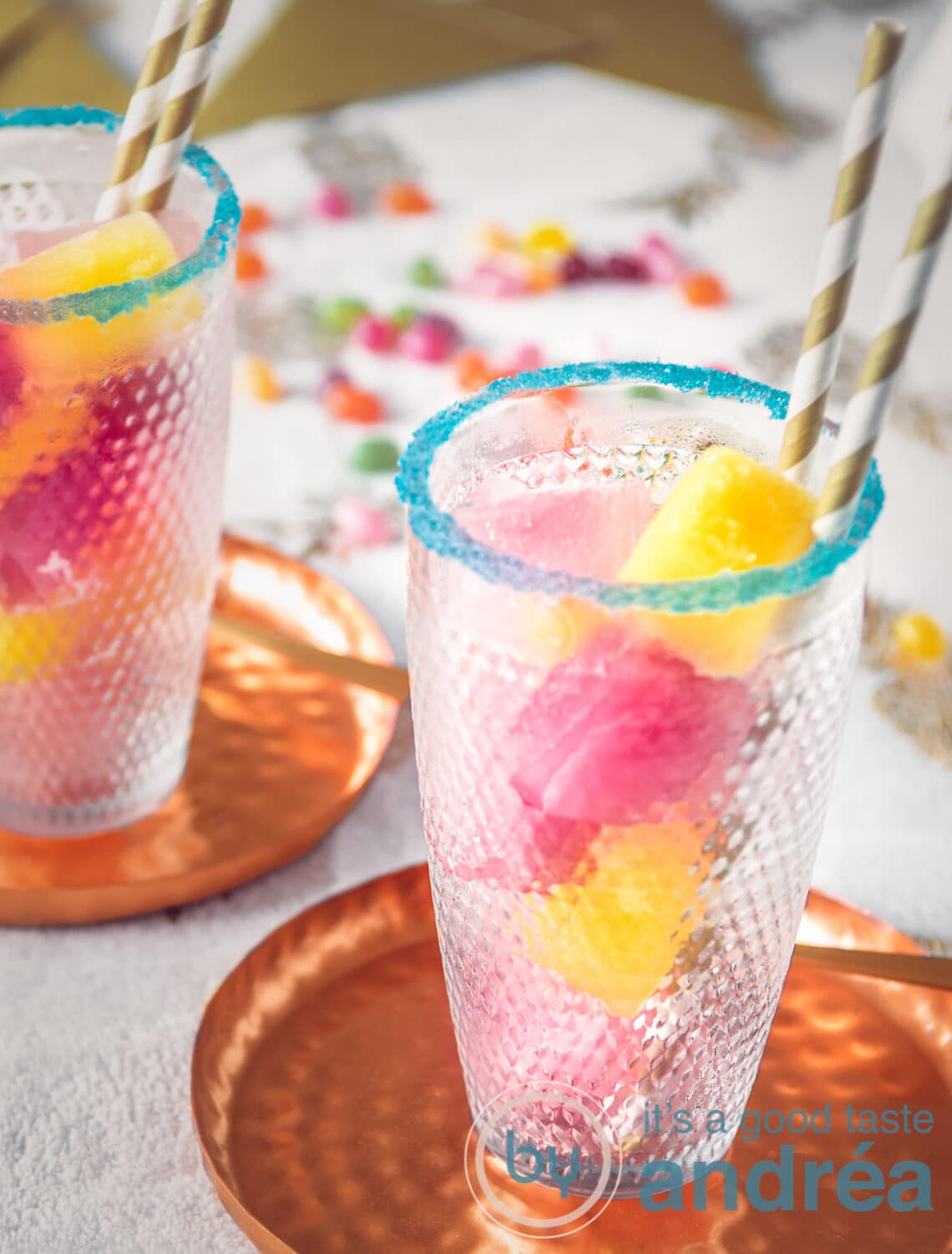 top glasses filled with colored ice cubes