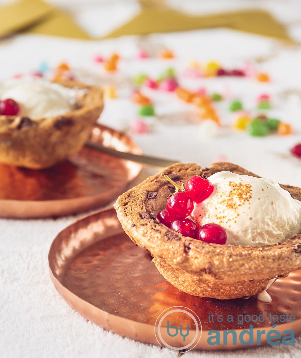twee zandkoek bakjes gevuld met vanille ijs en rode bessen