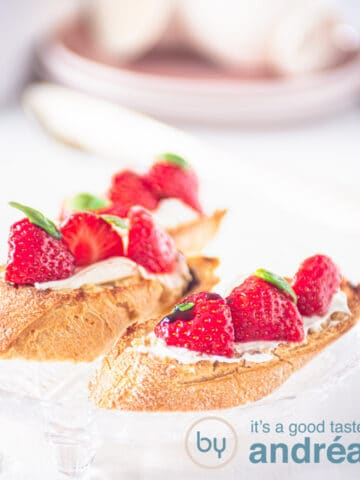 two bruschetta with marinated strawberries and mascarpone and some plates in the back