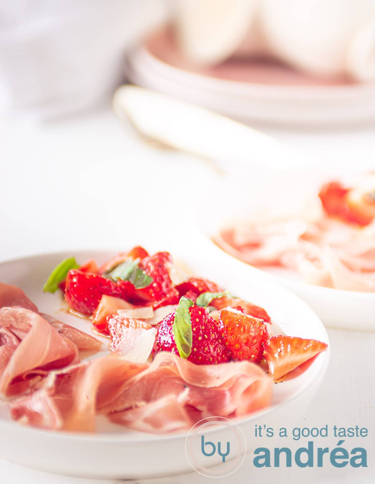 Marinated strawberries and Parmaham on a white plate with plates in the background