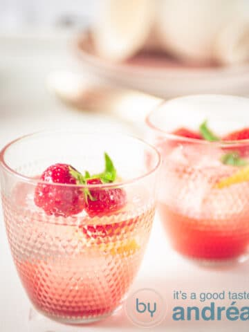 two glasses of strawberry lemonade with strawberry and lemon garnish
