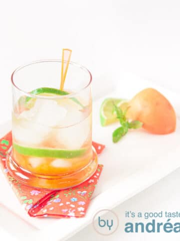 an Orange caipirinha with apricots in a cocktail glass and some garnish of apricots and lime