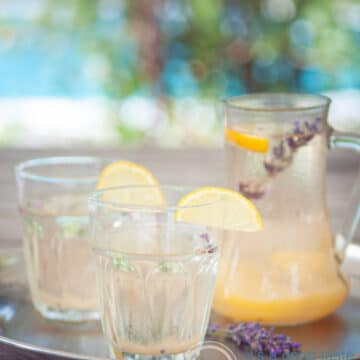 two glasses with lavender lemonade, garnished with lemon. A jar of lemonade and a summer background