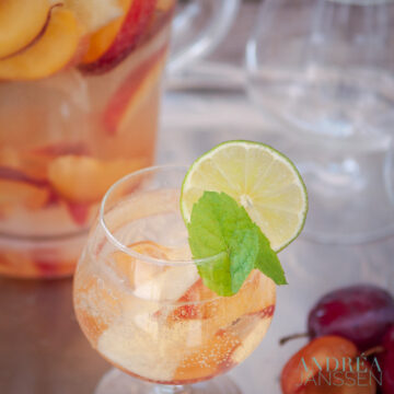 A glass of sangria Bianca with fresh fruit and a mint and lemon garnish. In the back a jar and some glasses