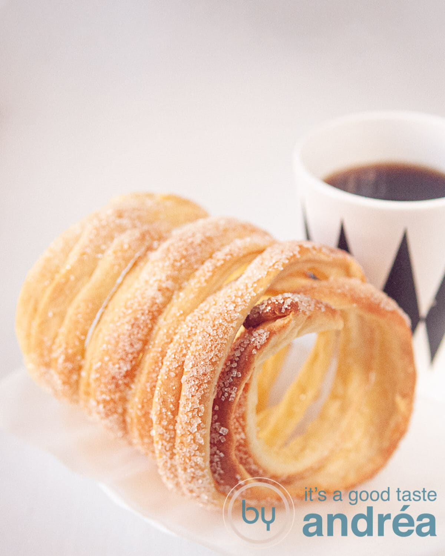 Een schoorsteen cake (koekje) op een witte achtergrond met een kopje koffie in een wit met zwarte ruitjes mok