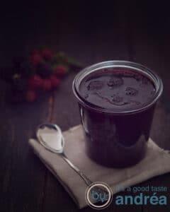 Een pot met Bramenjam met oregano op een bruine lap met een lepel