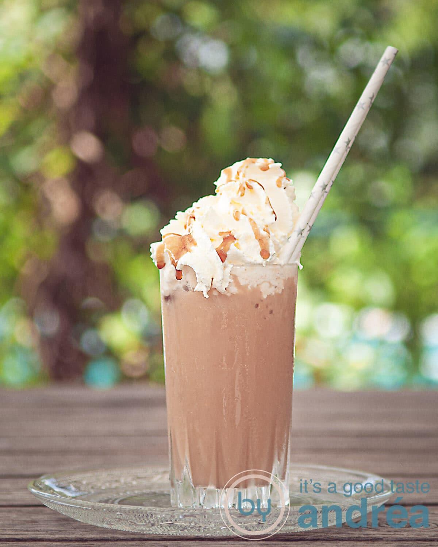 Een glas frappucino met slagroom en karamelsaus in een zomer achtergrond