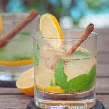A glass with Caipirinha with tea, lemon, ginger, int and cinnamon