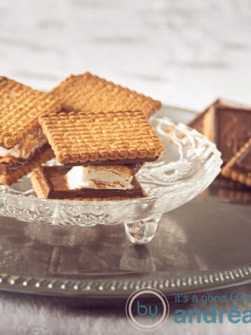 Three s'mores with chocolate biscuits on a glass plate. Some chocolate cookies in the back