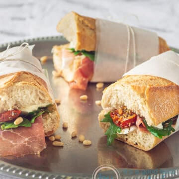 Three Italian flavored sandwiches with parma ham, arugula, sun dried tomatoes and Mozzarella wrapped on a silver plate