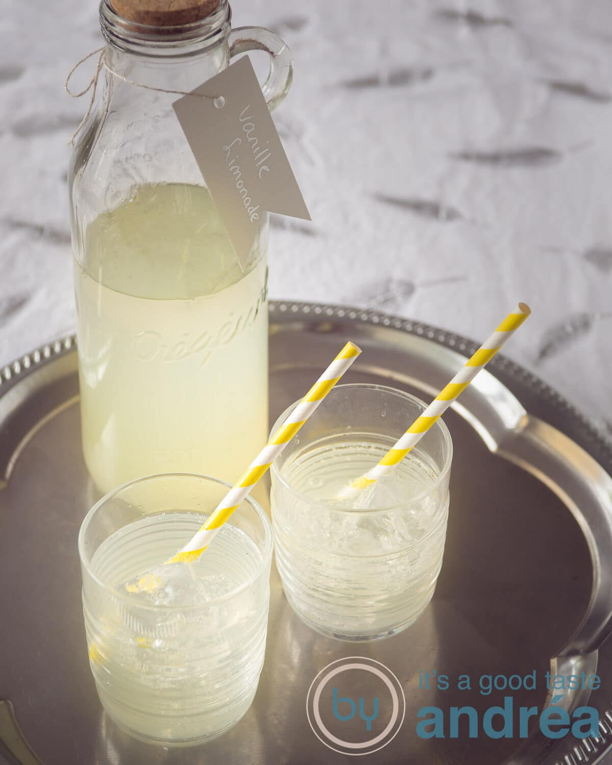 a bottle with vanilla lemonade and two glasses with straw filled with lemonade