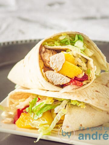 two wraps filled with chicken, lettuce, mango and tomato on a silver plate