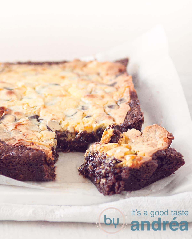 Een brownie met cheesecake waar een hoekje uit is gesneden op wit bakpapier