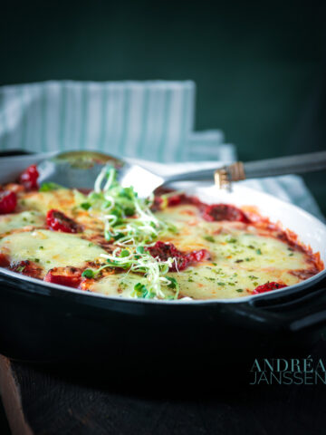 a black casserole dish with schnitzel, lost of vegetables and cheese