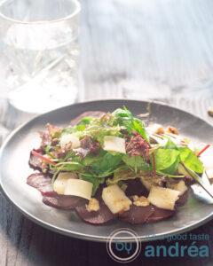 Carpaccio van bieten op een bord, met kaas, rucola, peer en walnoten