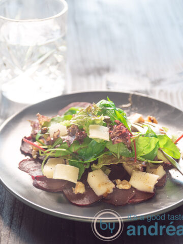 a white plate with beet carpaccio, pear, arugula, old cheese and walnuts
