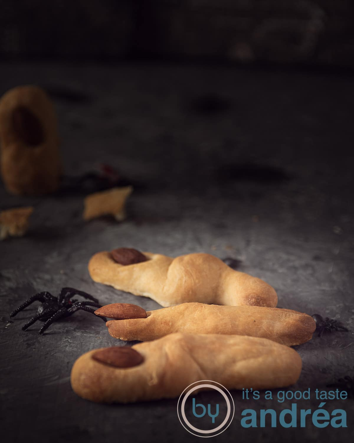 Three witch breadstick fingers on a grey background. An almond as the nail. Some spiders crawling around